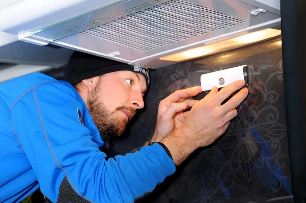 An electrician installing a Safera Airis stove guard under the cooker hood